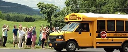 Parents waving at a bus